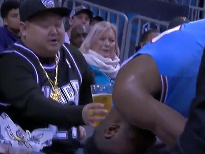 来一口?国王前排球迷向20岁的贾尔斯递上啤酒