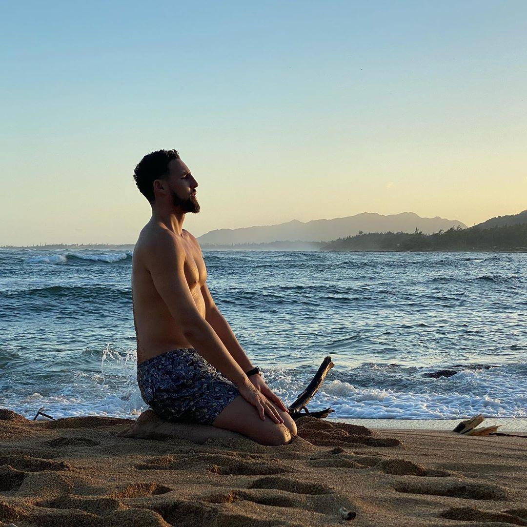 立地成佛!亚博棋牌娱乐汤普森跪坐在海边冥想的照片